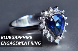 Blue sapphire as centerstone of an engagement ring with fourteen small diamonds around it.